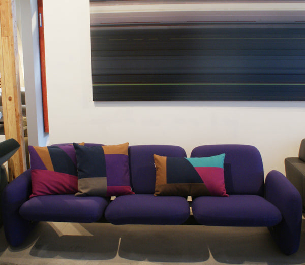 Purple and berry colored pillows on purple sofa from modern resale Los Angeles