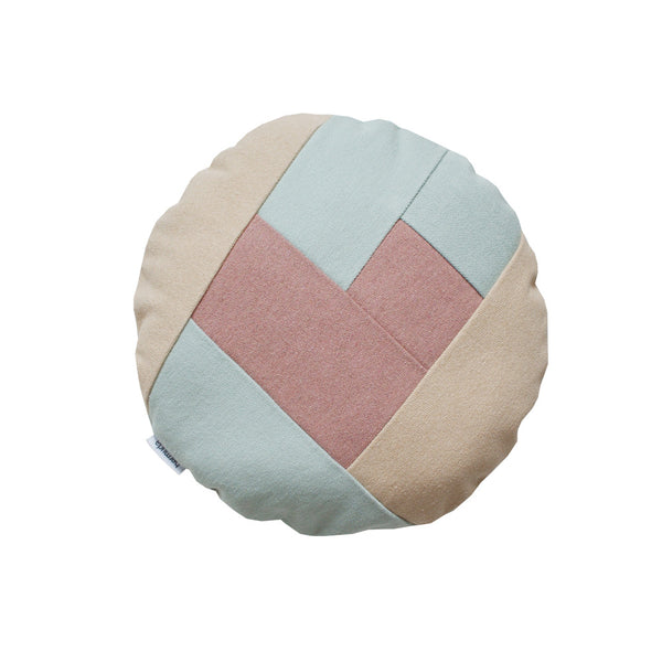 Adorable little round pillow in pastel colors with a pink heart on the front side. o