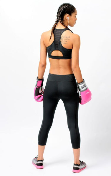 Back of woman wearing Essential Black Mesh Sports Bra by Epidemia Designs