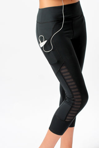 Close-up of Epidemia Designs Essential Black Capril Leggings with mesh panels and deep pocket holding a phone