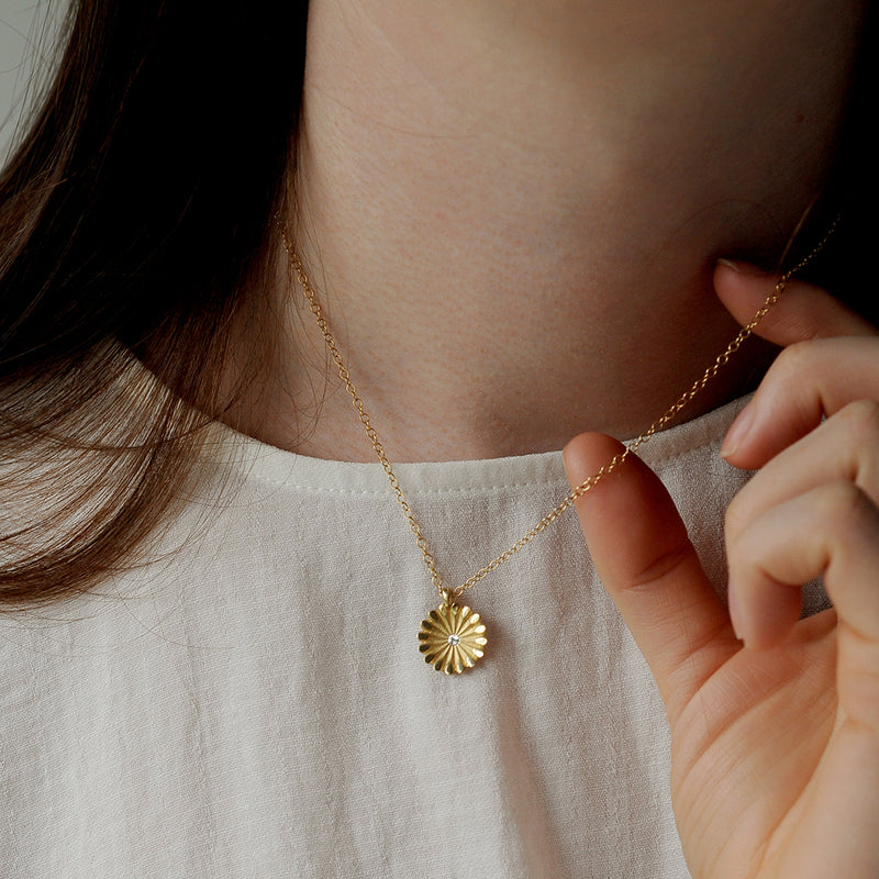 Model wearing ethical gold and diamond pendant