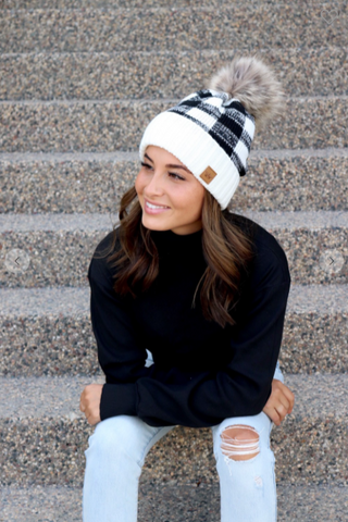 Women's Black and white buffalo plaid knit hat with pom accent.