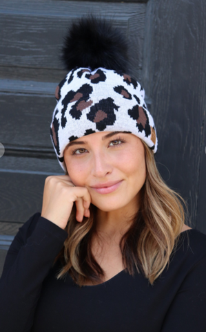 Women's White leopard fleece lined cable knit hat with pom accent.