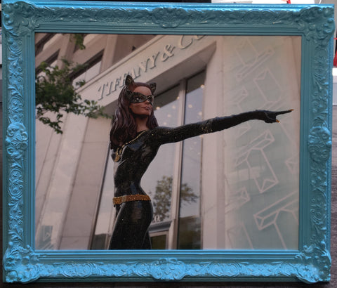 A toy figure Batwoman standing outside a Tiffany & Co store. The figure is pointing to a point not in the frame. It is on canvas, with glitter details. The frame is slightly ornate, and has been painted Tiffany blue.