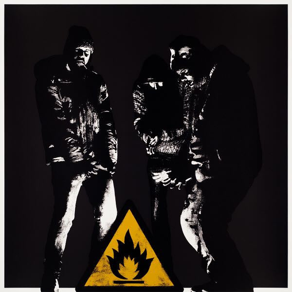 "Darkly coloured image of 3 people around the ""catches fire"" symbol in yellow and black. The characters are in black and whote. One is looking directly at the viewer"