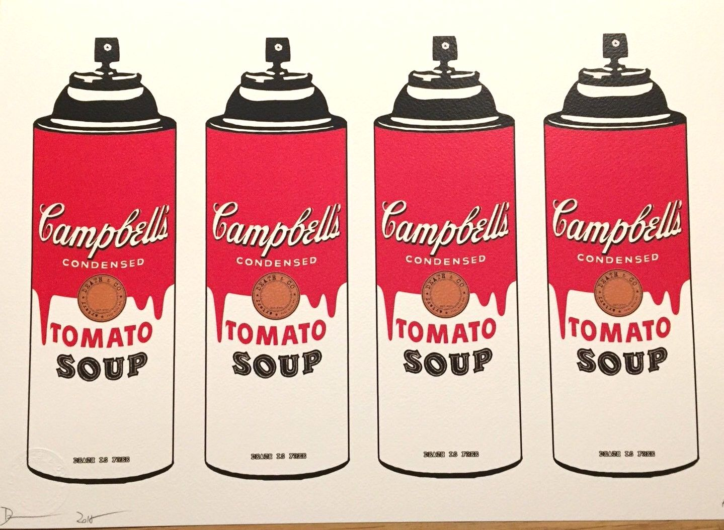 4 spray cans that are labeled as if they were Campbell's tomato soup cans. The labels are bright red and are dripping down like spray paint.
