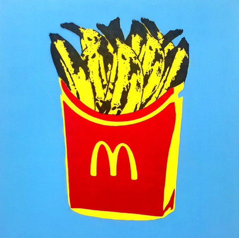 Red and yellow fry container with the MacDonald's  golden arches logo on the front of the box, but it contains bananas. The background is blue.