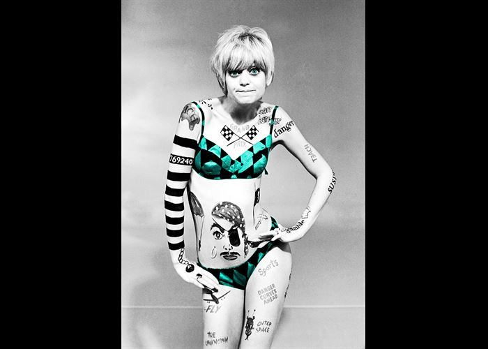 Woman posing with a funny expression, wearing a bikini. Her bikini is turquoise, and she is decorated in tattoos. It is black and white except for the bikini
