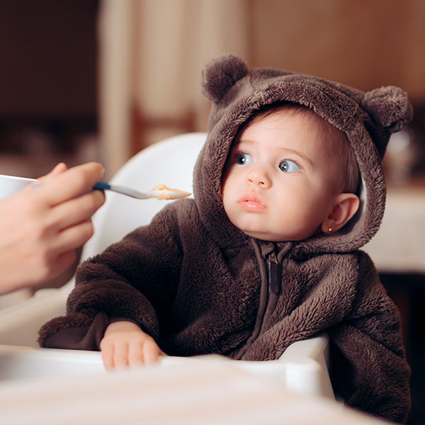 Child looking scared at spoonful of food