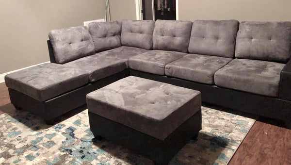 Grey reversible microfiber sectional with drop down cup holders and storage ottoman