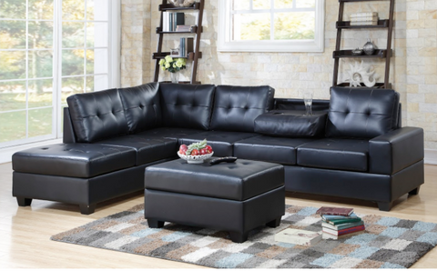 Faux black leather reversible tufted sectional with drop down cup holders and storage ottoman