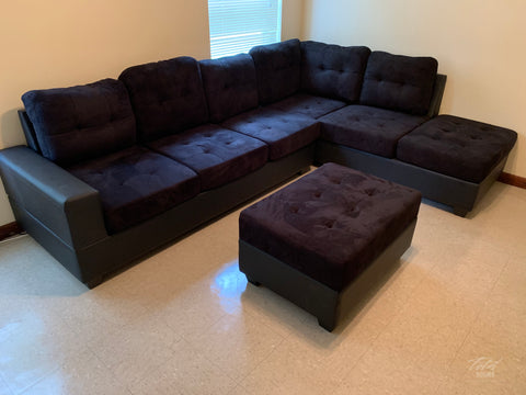 Black reversible microfiber sectional with drop down cup holders and storage ottoman