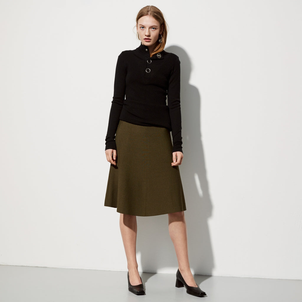 FWSS Turn Around is a high waisted midi flared skirt in flattering rayon jersey. Features zipper closure in the back and raw edged hem.