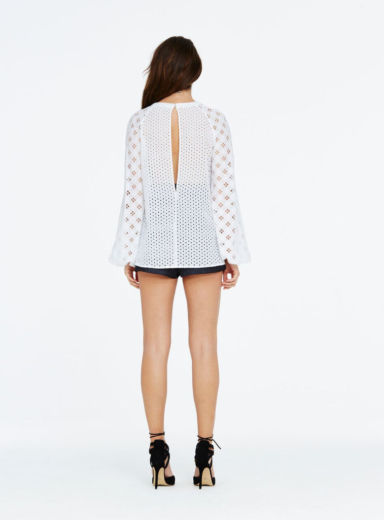 The One Call Away blouse is a fresh Spring piece cut in a gorgeous 100% cotton broderie anglaise lace. Showing just a hint of skin, the top was designed with a keyhole cutout on the back and highlights the shoulders and décolletage with a peekaboo feature. Wear tucked into silk shorts for a polished look.