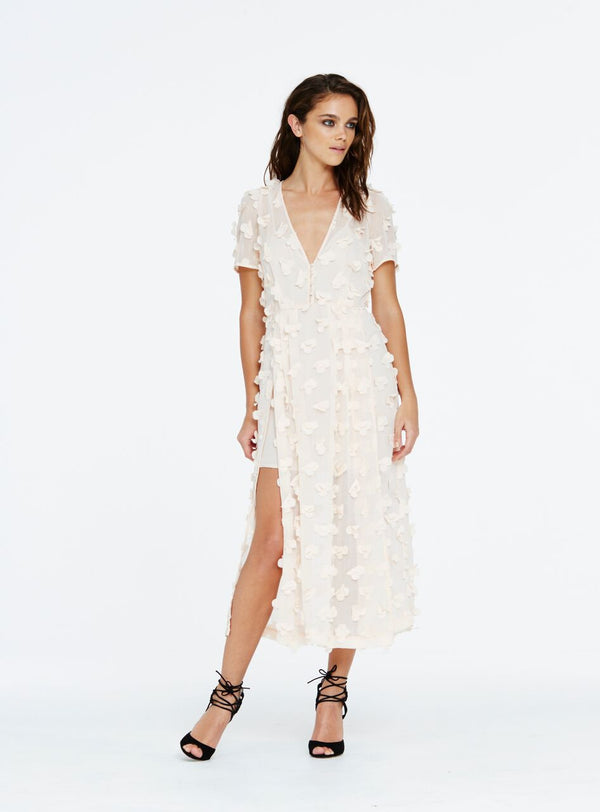 The 'Could It Be Magic' dress is universally flattering. This fluid style is a shift shape and sits loosely around the waist and hips. The cap sleeve is made up of soft romantic petal applique and finishes in a short sleeve style.  This dress is of a sheer kind, so this style includes a plain slip to be worn underneath. Ground this style by pairing it with pretty sandals for a day time look.