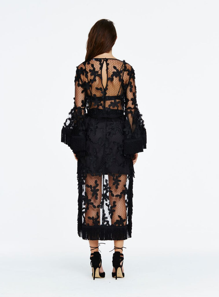 The 'California Sun' top is a divine cropped length style, featuring delicate floral lace applique and soft satin-finished fringe trim on the sleeves. A simply stunning piece, the intricate floral lace and flared sleeves of the cropped top make a bold statement when layered over a chic bralette and paired with the matching 'I Hope You Dance' skirt