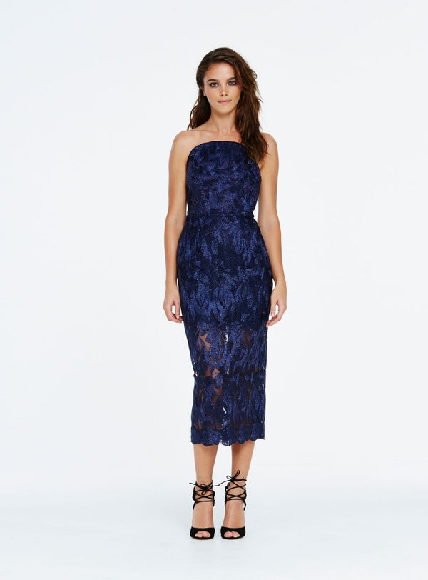 A standout party choice, this lurex embroidered fabric is detailed with metallic lace in a leafy pattern. Complete with internal boning for support, this slim-fit style has a high waist seam and pencil midi skirt for feminine appeal. The shaped bodice has a curved look around the neckline which frames the shoulders and decolletage. This style is fully lined, ending mid thigh and then becoming sheer until mid calf, finishing with a scallop at the hem.