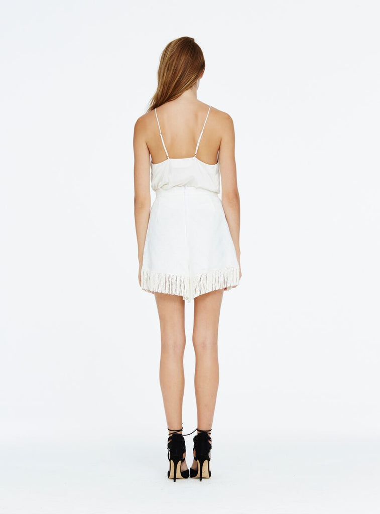 The high waisted style of the 'Eagles Dare' skort is the perfect accompaniment to a chic tucked in silk cami. Designed with a unique zig-zag jacquard fabric, the mini length skort features a delicate fringe trim across the front and hemline of the skort. Create a flattering cinched in silhoutte by tucking in a classic style T shirt for an effortless daytime look or amp it up with a solid ankle boot.