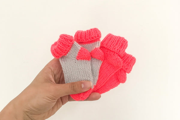 Women's hand holding two pairs of baby socks in neon coral and grey