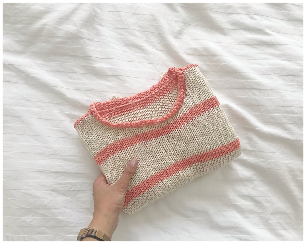 Folded Cream and Peach striped handknitted cotton tee held by hand