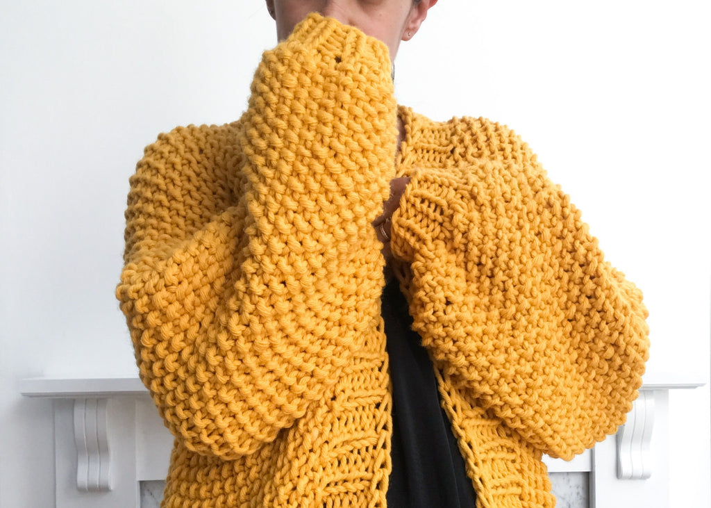 Sleeves of oversized yellow knit cardigan