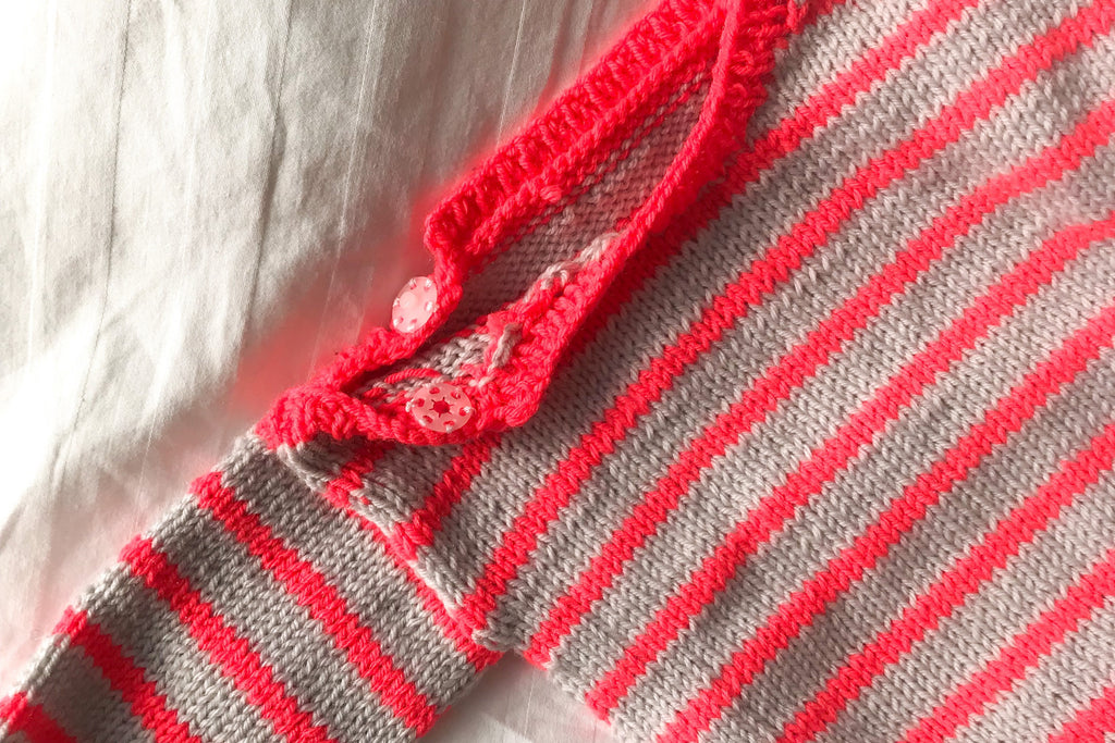 neck closure of handknitted striped baby jumper in grey and neon coral