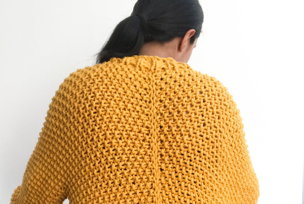 Back of oversized yellow cardigan