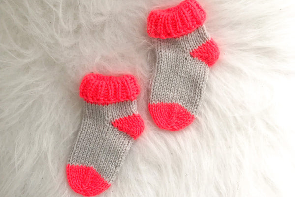 Pair of newborn socks in neon coral and grey on white background