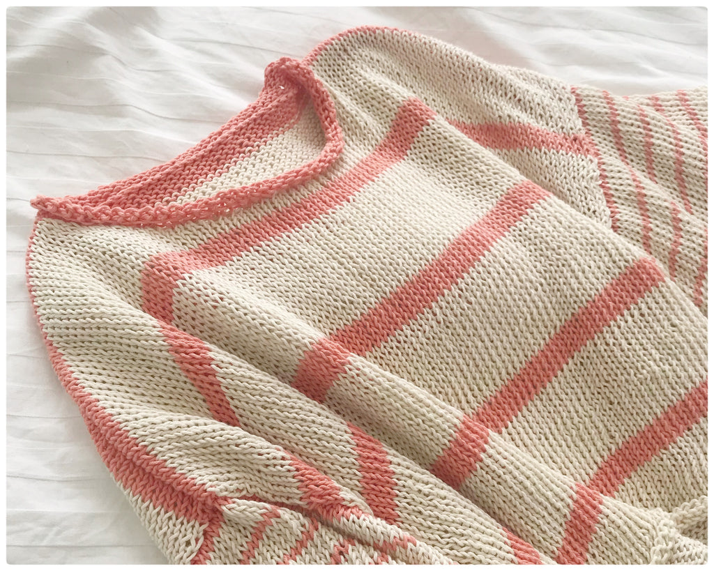 Cream and Peach handknitted cotton stripe tee shirt lying on white bed