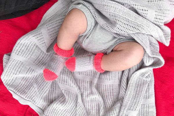 Baby's legs wearing neon coral and grey socks on a grey cotton blanket