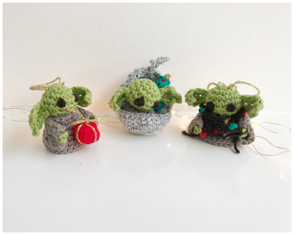 3 baby yoda Christmas tree decorations with fairy lights behind
