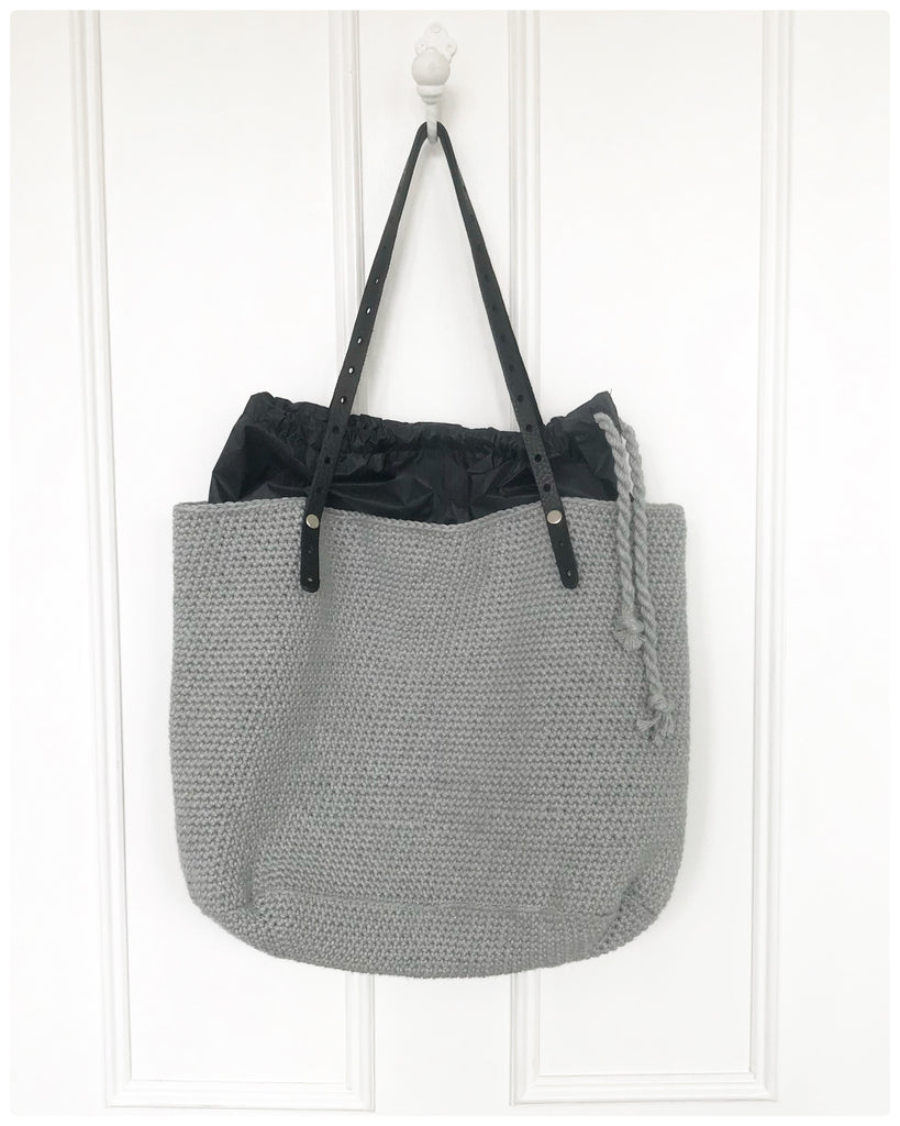 Crochet Baby-thing Bag finished, hanging on white door