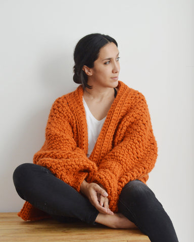 Woman seated wearing orange chunky crochet cardigan, black jeans and white tee against white background
