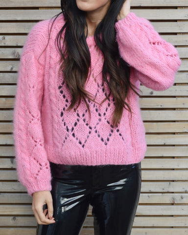 Woman wearing pink lace mohair jumper and black patent trousers next to fence