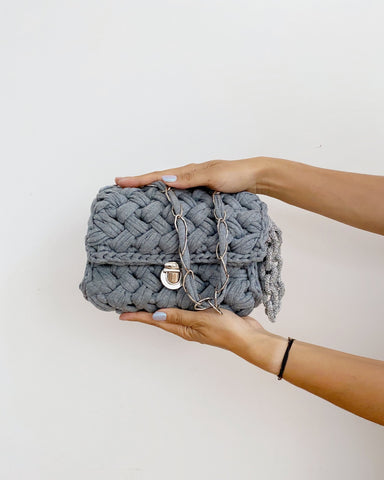 Grey crochet handbag with silver chain and silver clasp held between two hands