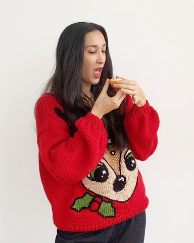 Woman with dark hair wearing red christmas jumper with reindeer image on front, eating mince pie
