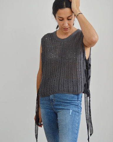 Woman wearing grey crochet vest with black ribbon laced sides and blue jeans