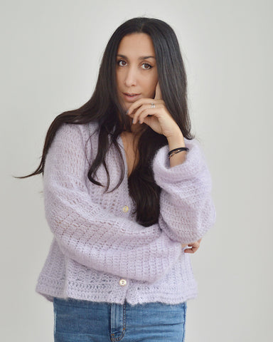 Woman with dark hair and arms crossed, wearing lilac mohair crochet cardigan and blue jeans