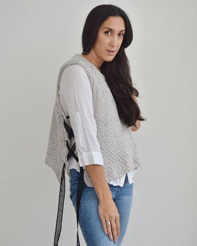 Woman wearing white shirt with light grey knit vest with black ribbon laced sides