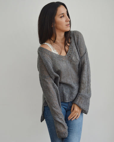 Woman wearing oversized grey mohair knitted V neck sweater and jeans
