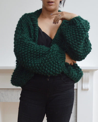 Woman wearing green chunky knit cardigan and black jeans, with one arm crossed at waist