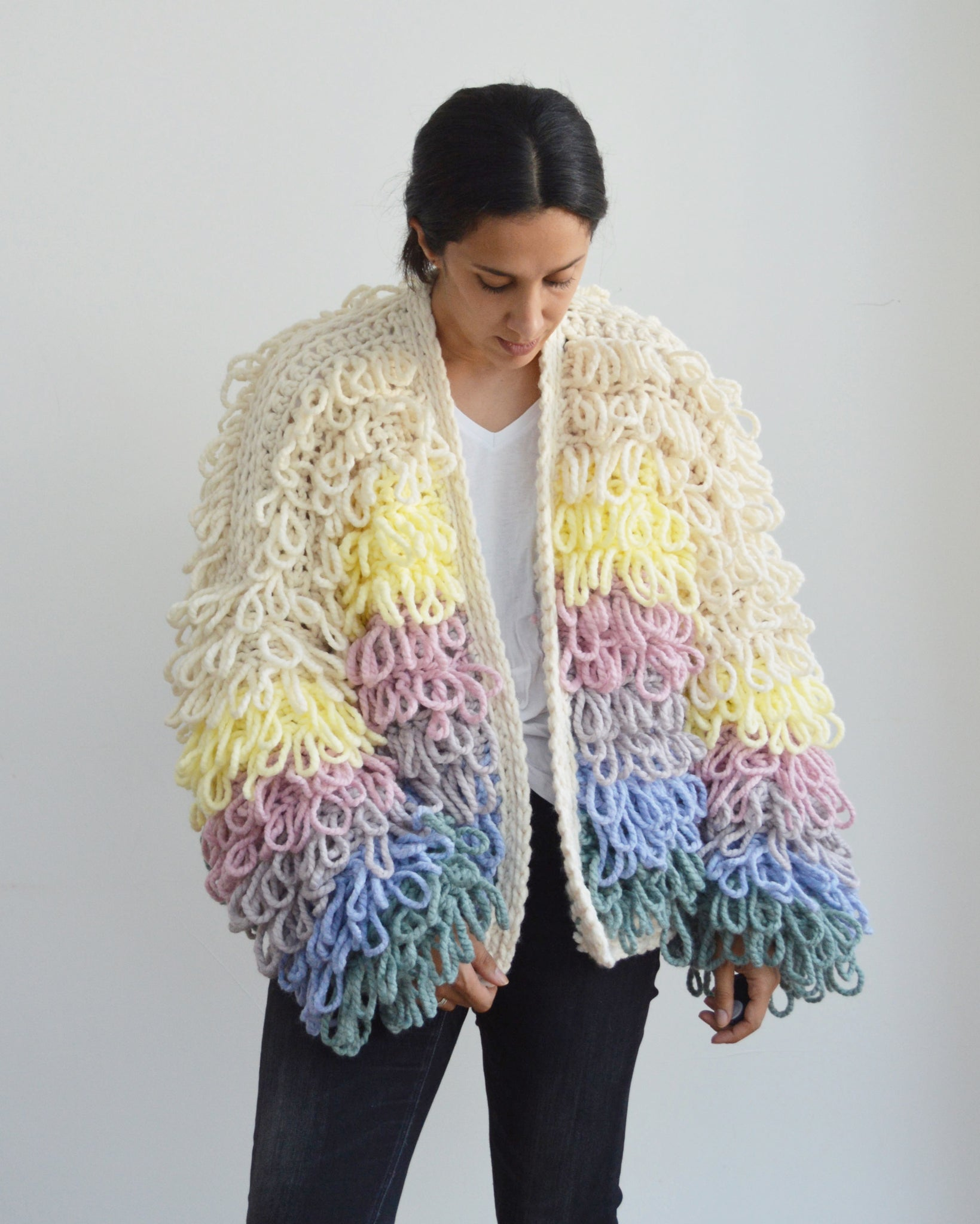 Woman looking down wearing loopy pastel crochet cardigan against light background