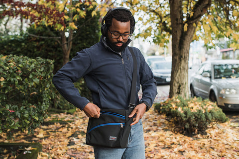 Man wearing headphones and an Icon messenger bag in Black 525d/Island Zippers on a late fall day.