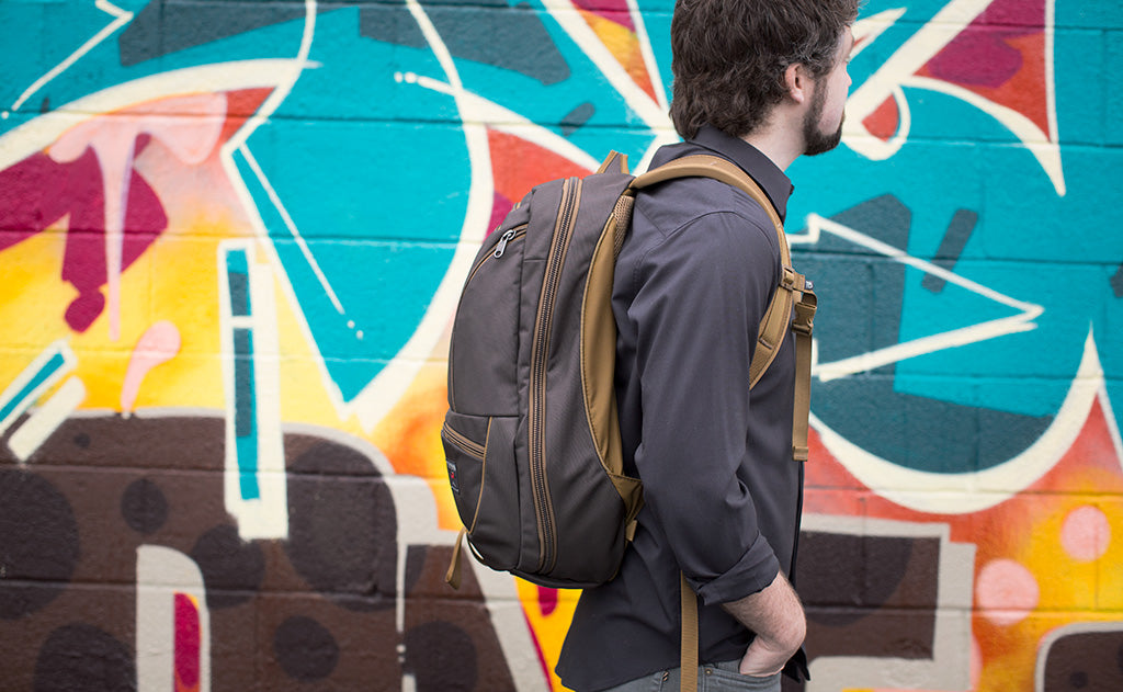 Man wearing the Synik 30 in Ursa brown in front of a wall of street art in the city.