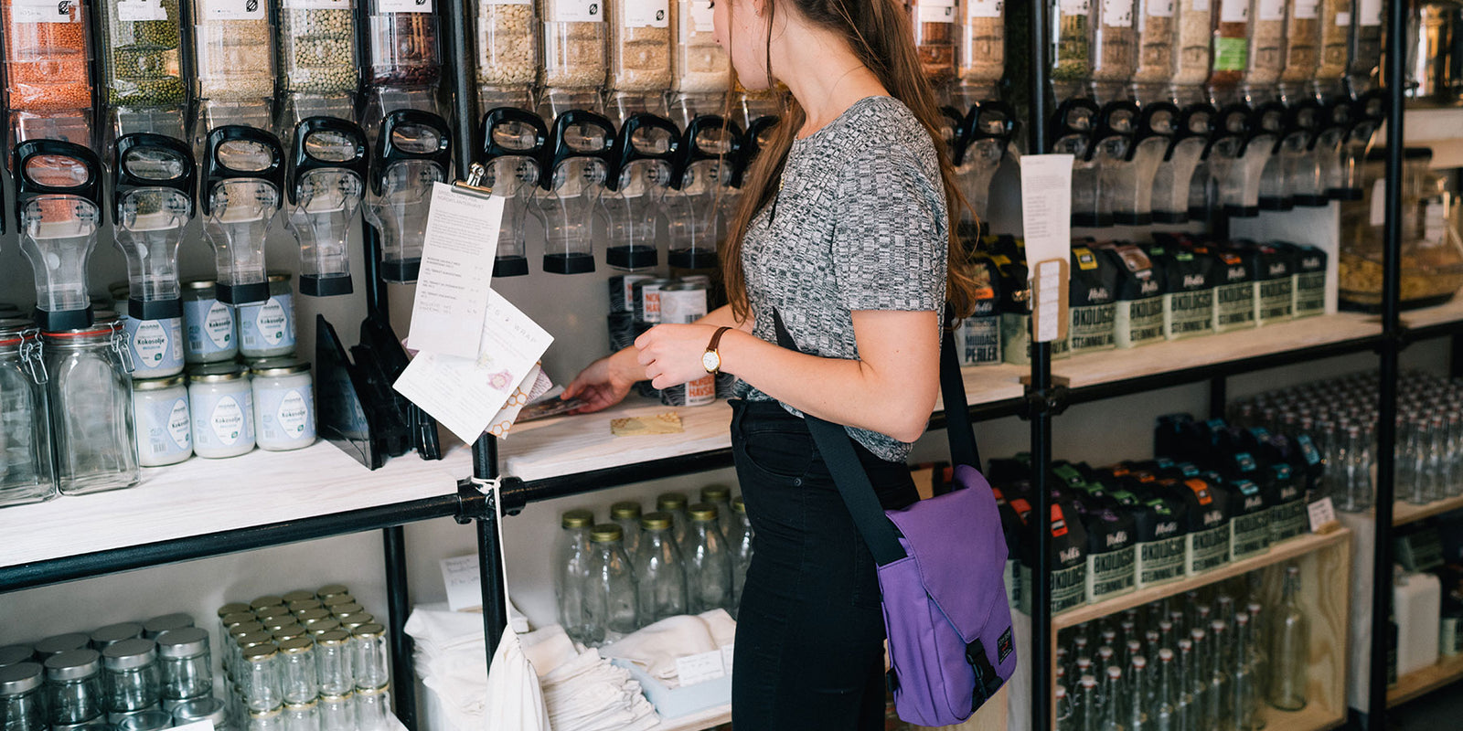 Woman buying bulk items at a natural food store wearing the Small Cafe Bag