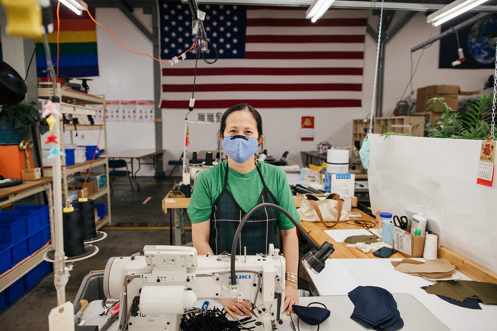 Honguyen, Sewing Supervisor In Training, stands in front of Rainbow, American, and Earth flags at the TOM BIHN factory in Seattle.