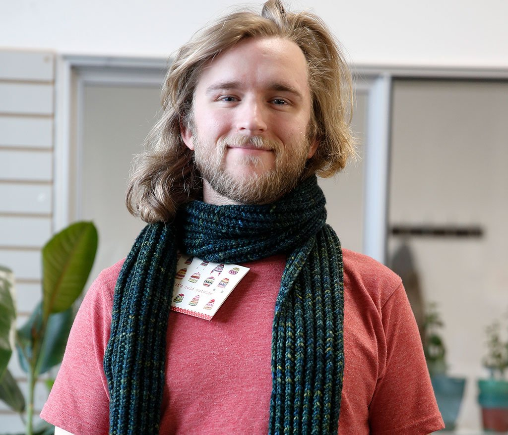 Matt, Shipping Lead at TOM BIHN, wearing a scarf knitted for him by the Ravelry group.