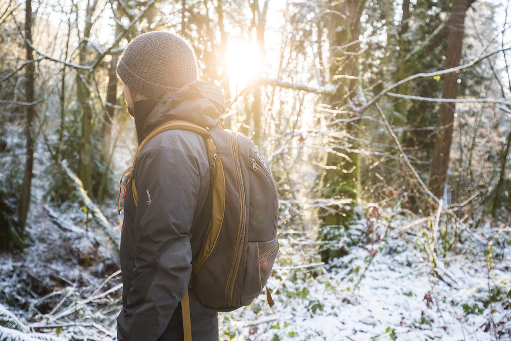 Man wearing the Guide's Edition Synik 30 in Ursa brown while hiking in the snowy woods in the late afternoon sun.