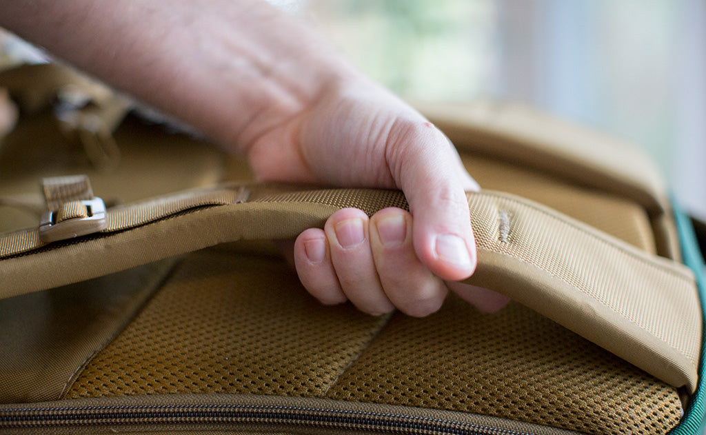 Man grabbing the Edgeless strap of a Synik 22; showing how thick and comfortable they are.