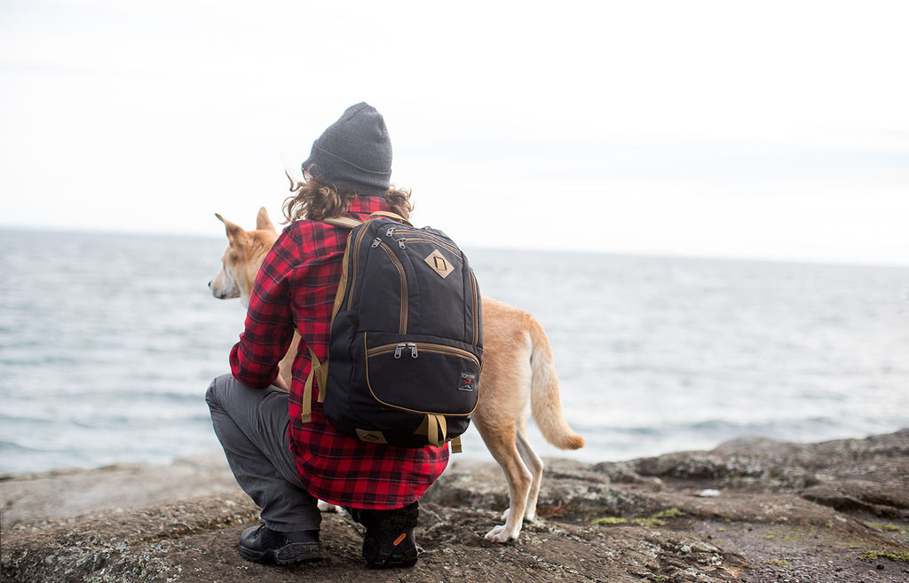 Man with his dog on rocks overlooking the ocean. Wearing a Guide's Edition Synapse 25 in Black.